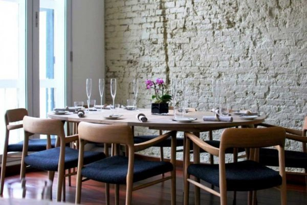 wooden-dining-chairs-with-padded-seats-across-whitewash-brick-wall-above-walnut-laminate-flooring-600x401